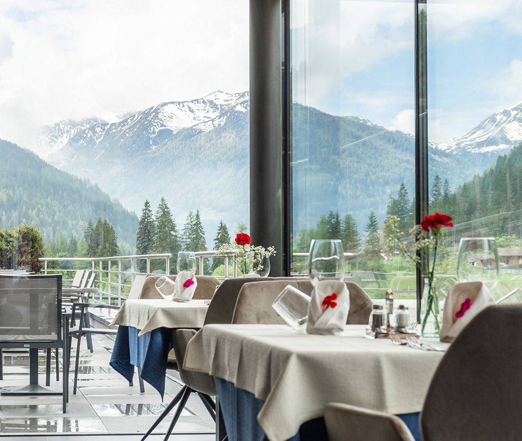 Bright dining room with floor-to-ceiling glass fronts and a view of the surrounding mountains and forests